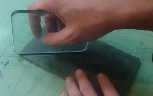 緑の革のキーケースのトコ面をガラス板で磨く