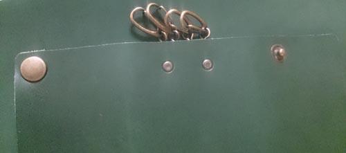 緑の革に両面カシメでキーケースを取り付け